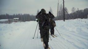 小组战士在滑雪跑在有武器的森林 夹子 有AK-47步枪和枪榴弹发射器跑的战士