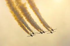 小组战斗机飞机飞行与烟轨道反对与云彩的橙色天空 库存照片