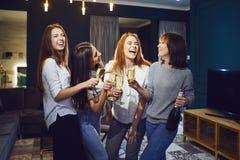 小组戴香槟眼镜的妇女获得乐趣在党在家 免版税库存图片