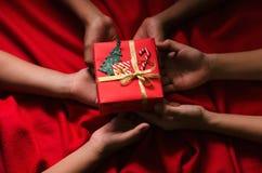 小组手孩子举行圣诞节在红色背景的礼物盒 库存图片