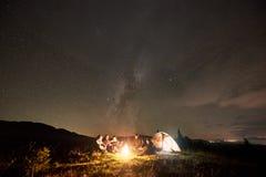 小组有吉他的游人通过烧篝火在与银河星座的黑暗的满天星斗的天空下 图库摄影