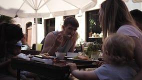 小组有孩子的年轻人吃午餐在街道上的一个咖啡馆 股票视频