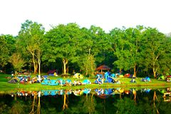 小组有小森林和湖的幸福人野营的帐篷 库存照片