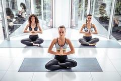 小组有思考在瑜伽姿势的教练员的年轻被集中的妇女 免版税图库摄影