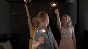 小组有拿着闪烁发光物的男性标题的愉快的人在党跳舞和微笑 股票视频
