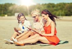 小组有智能手机的愉快的妇女在海滩 免版税库存图片
