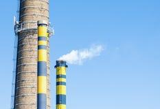 小组有烟的工业烟囱反对蓝天 库存照片
