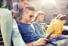 小组有片剂个人计算机的学生在校园 免版税库存图片