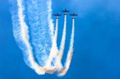 小组有白色烟踪影的白色涡轮螺旋桨发动机飞机反对蓝天的 免版税图库摄影