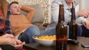 小组朋友一起坐沙发、观看的电视和饮用的啤酒 免版税库存照片