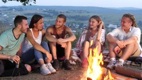 小组朋友在与温暖的饮料的一个营火旁边坐并且谈话 股票视频