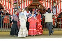 小组朋友在传统服装和享用穿戴了在SevilleÂ的4月市场 库存照片