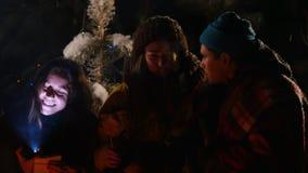 小组朋友在坐在篝火附近的冬天森林里,听故事和得到惊吓 关闭面孔 股票视频