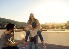 小组朋友在屋顶大厦发笑在日落 免版税库存照片