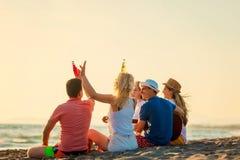 小组朋友在海滩使用 免版税库存图片