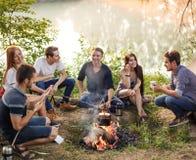 小组朋友在阵营火附近坐并且准备香肠 免版税图库摄影