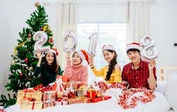 小组朋友是亚裔人,并且妇女装饰了圣诞树 免版税库存图片