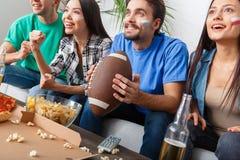 小组朋友观看在五颜六色的衬衣橄榄球的体育迷比赛 库存图片