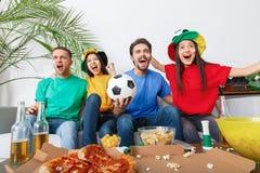 小组朋友观看在五颜六色的衬衣胜利祝贺的体育迷比赛 免版税库存图片