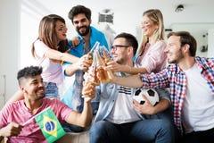 小组朋友观看足球比赛的体育迷敬酒 免版税图库摄影