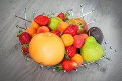 小组果子:葡萄柚、strawberrie、杏子、西番莲果和梨 在一个金属花瓶的果子在木背景 免版税库存照片