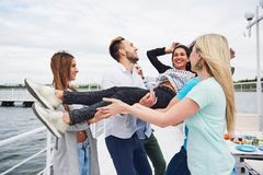小组海滩的愉快的朋友,扔一名愉快的妇女的人 免版税库存图片