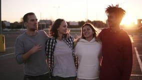 小组混合的族种朋友走拥抱和一起谈话在城市 他们是两个女孩和两个男孩他们的 股票录像
