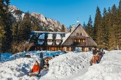 小组游人在山小屋前面坐并且享用太阳, Koscieliska谷 免版税库存图片