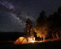 小组游人在帐篷阵营神色的夜森林里在灼烧的火在满天星斗的天空下 图库摄影