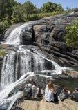 小组游人坐岩石靠近贝克的瀑布在国立公园 图库摄影