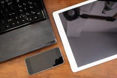 小组现代电子设备、计算机膝上型计算机、数字式片剂和流动巧妙的电话在木桌上 库存图片