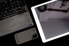 小组现代电子设备、计算机膝上型计算机、数字式片剂和流动巧妙的电话,在黑背景 剪报 图库摄影