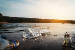 小组瓶塑料在河 免版税库存图片
