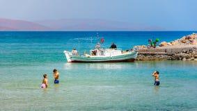 小组男孩获得乐趣在美丽的海滩在Istron,克利特,希腊 免版税库存图片