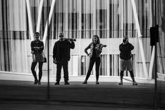 小组画象站立在现代大厦前面的年轻和可爱的人民 免版税库存照片