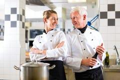 小组的二位主厨在旅馆或餐馆厨房里 免版税库存照片