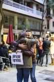 小组的行动人释放在巴塞罗那街道,题字上的拥抱用在海报自由拥抱的西班牙语 图库摄影