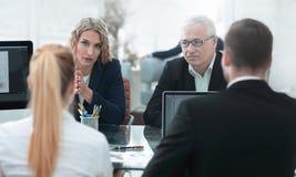 小组确信的商务伙伴谈论纸在会议上 免版税库存照片