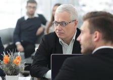 小组确信的商务伙伴谈论纸在会议上 库存图片