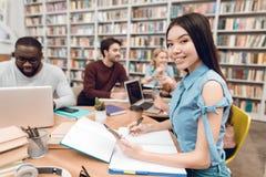 小组种族多文化学生在图书馆里 亚洲女孩附注采取 免版税库存照片