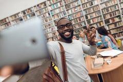 小组种族多文化学生在图书馆里 采取在电话的黑人selfie 免版税库存图片