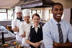 小组站立与胳膊的旅馆职员横渡在厨房里 库存照片