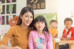 小组类的基本的年龄孩子与获得的老师学会和乐趣 免版税图库摄影