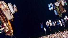 小组老货船,拖轮,钓鱼船和小船在海岸在岩石附近 免版税库存图片