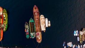 小组老货船,拖轮,钓鱼船和小船在海岸在岩石附近 库存照片