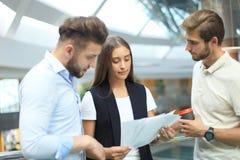 小组聪明的便衣的年轻现代人开突发的灵感会议,当站立在创造性的办公室时 库存图片