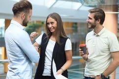 小组聪明的便衣的年轻现代人开突发的灵感会议,当站立在创造性的办公室时 库存照片