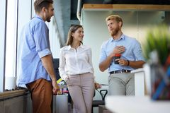 小组聪明的便衣的年轻现代人开突发的灵感会议,当站立在创造性的办公室时 免版税库存照片