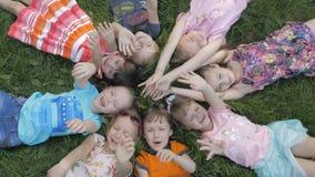 小组说谎在草的幼儿园孩子在公园和放松与微笑 股票视频