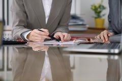 小组谈论的商人和的律师合同,当坐在桌上时 妇女院长采取笔为 库存照片